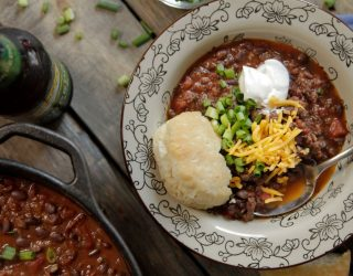 bowl of black bean chili with bread and toppings