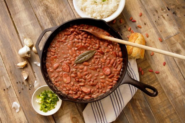 cast iron pot of red beans on table with wooden spoon