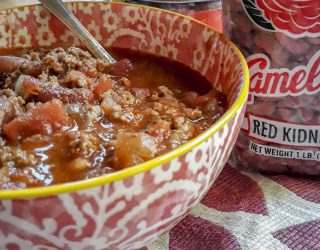 bowl of chili with can of seasoning and bag of beans
